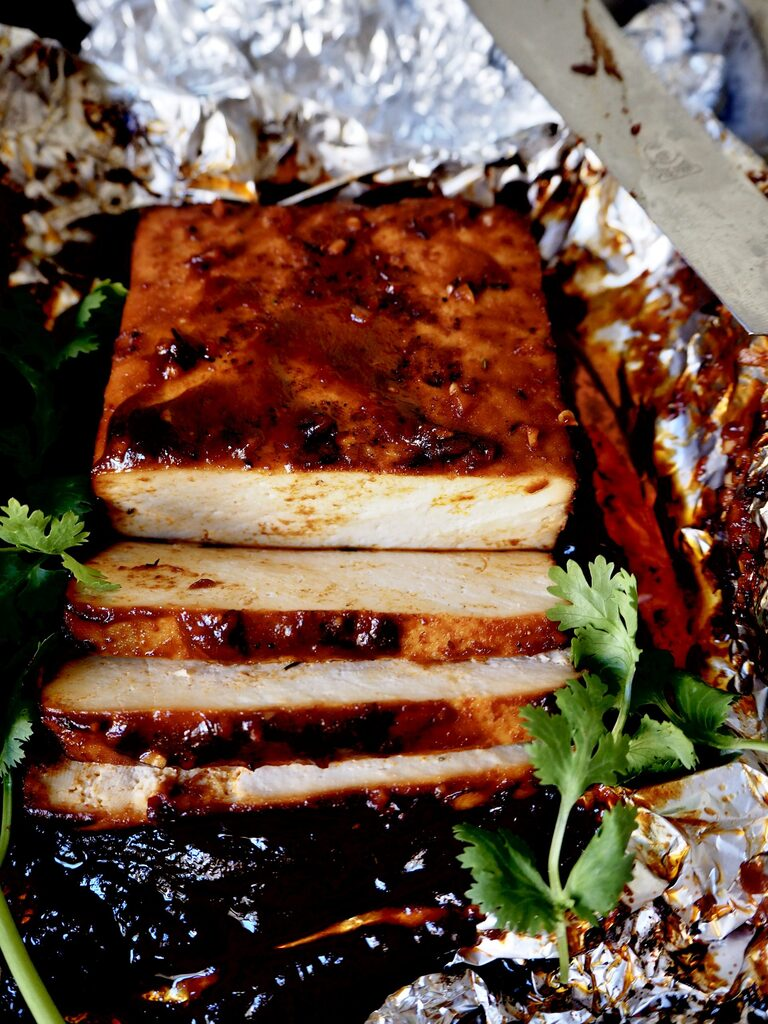 sliced marinated tofu with coriander in tin foil viewed from the front