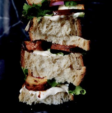stacked sandwich front view with aioli and tofu and greens against dark background