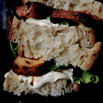 de sandwich van dichtbij, brood, tofu, aioli, en sla gestapeld tegen een donkere achtergron
