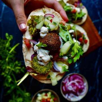 pita with falafel held by hand with sour cream, tomato cubes, cucumber, parsley with more falafel in the background and a bowl of red onion against a dark backdrop