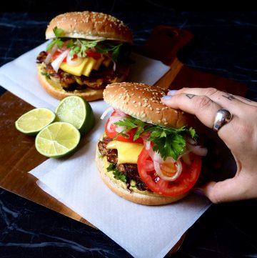 dos hamburguesas con mango con una mano cogiendo la de derecha.