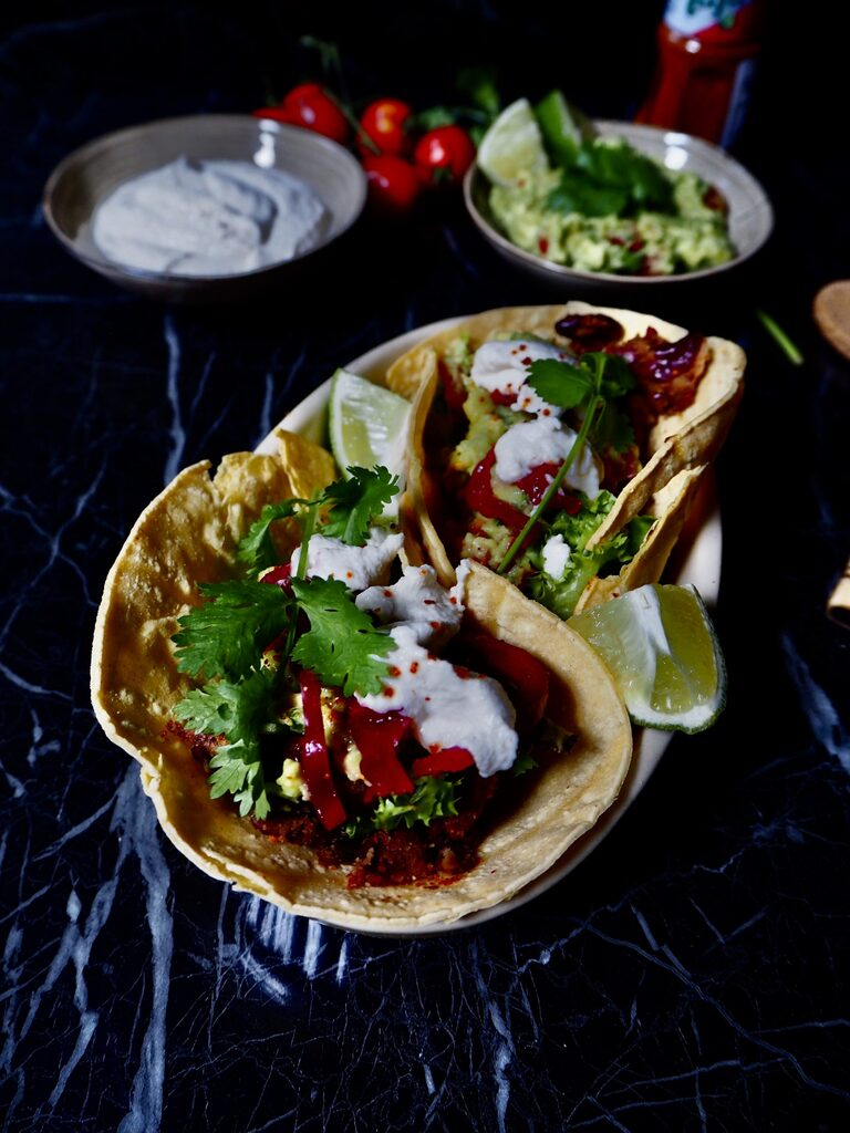 15 minute vegan tacos in a bowl seen from the front with two small bowls in the background with sour cream and guacamole. Against a dark backdrop