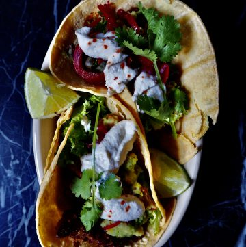 15 minute vegan tacos seen from above filled with beans, guacamole, sour cream, coriander, and lime wedges against a dark backdrop