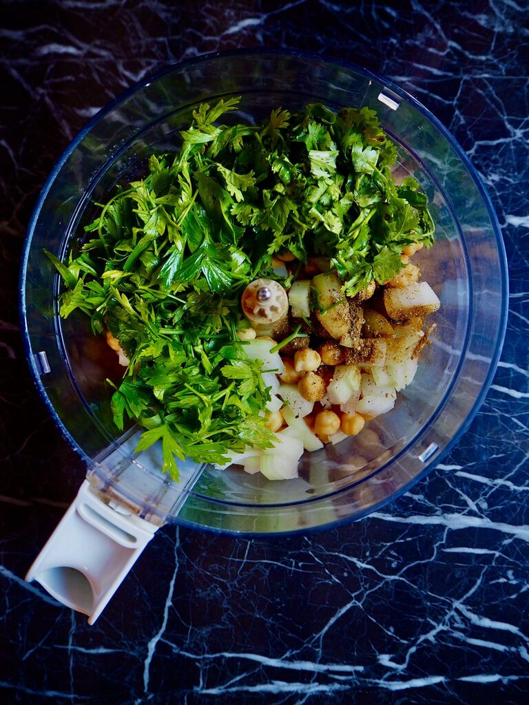 food processor filled with soaked chickpeas, onion, garlic, spices, coriander, and parsley.