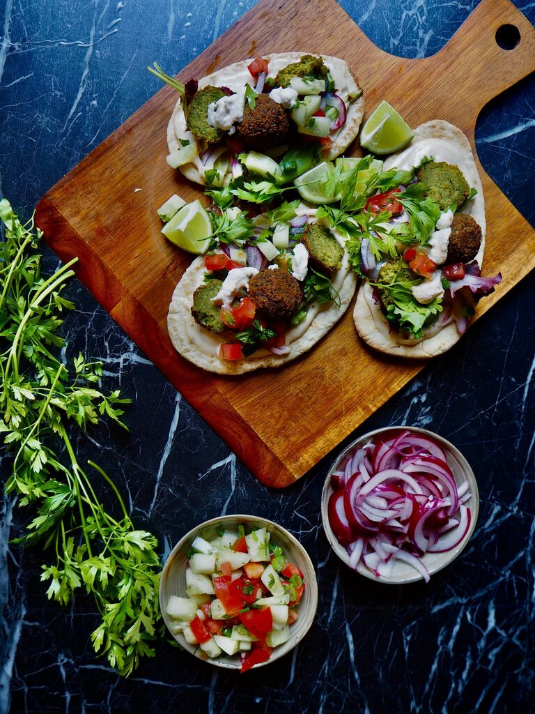 three pita's with falafel and topping on wooden board. a bunch of fresh parsley to the left, two small bowls with cucumber and tomato, and pickled red onion. against a dark backdrop