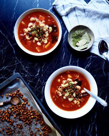 de abajo hasta arriba: una bandeja con croutons de garbanzos, dos bols de minestrone, un bol pequeño con hierbas, y una toalla de cocina