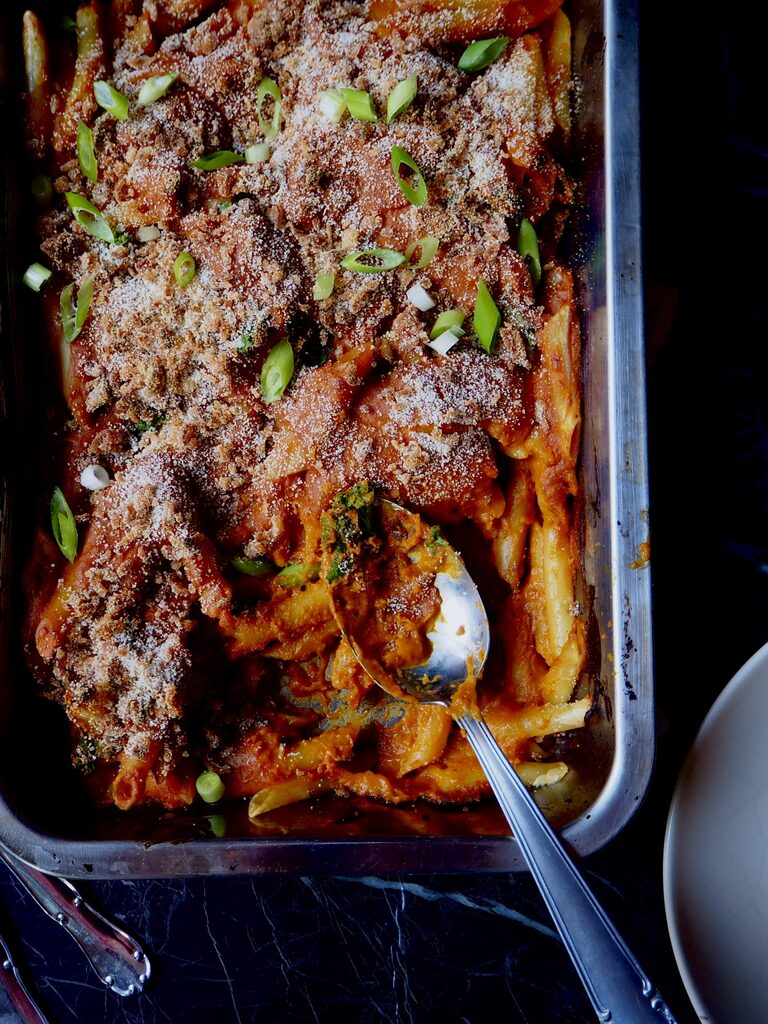 booze vegan mac 'n cheese seem from above with a serving spoon in the right bottom corner