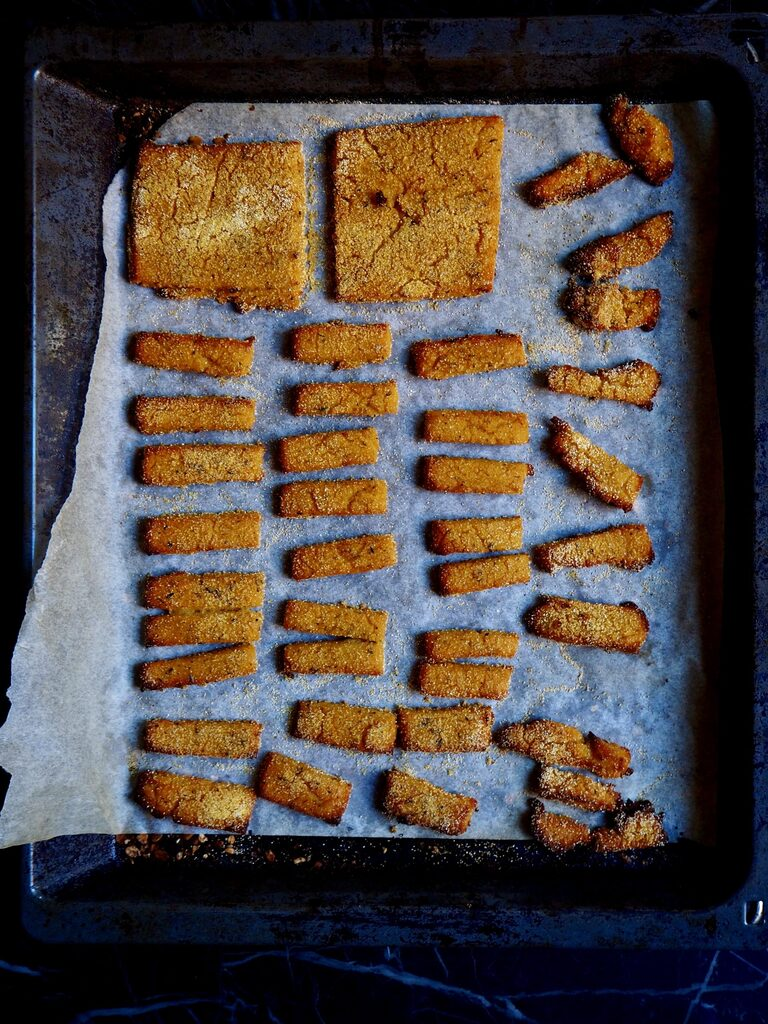 crispy polenta fresh from the oven seen from above on some parchment paper