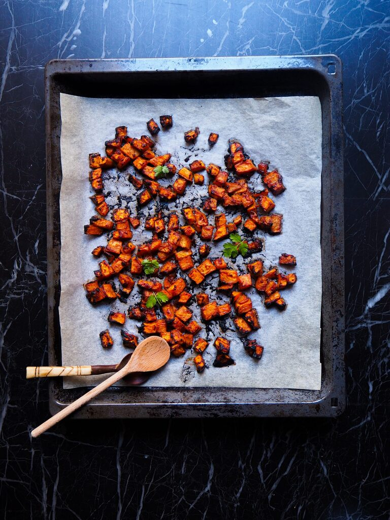 miso glazed sweet potato cubes just from the oven seen from above on a baking sheet with parchment paper and two spoons