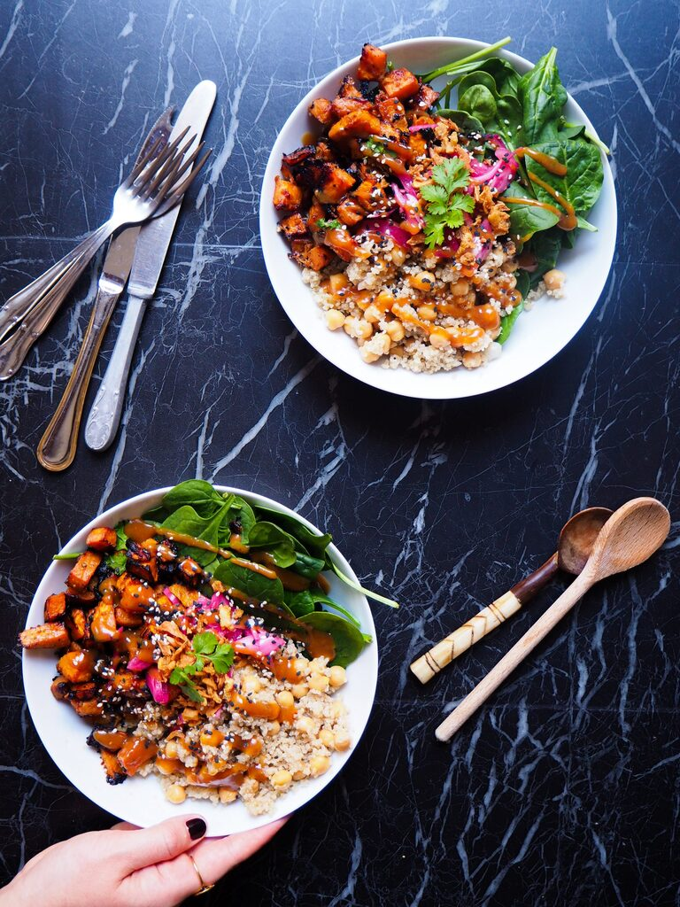two miso sweet potato and quinoa bowls seen from above against a dark backdrop and a hand holding one of the bowls