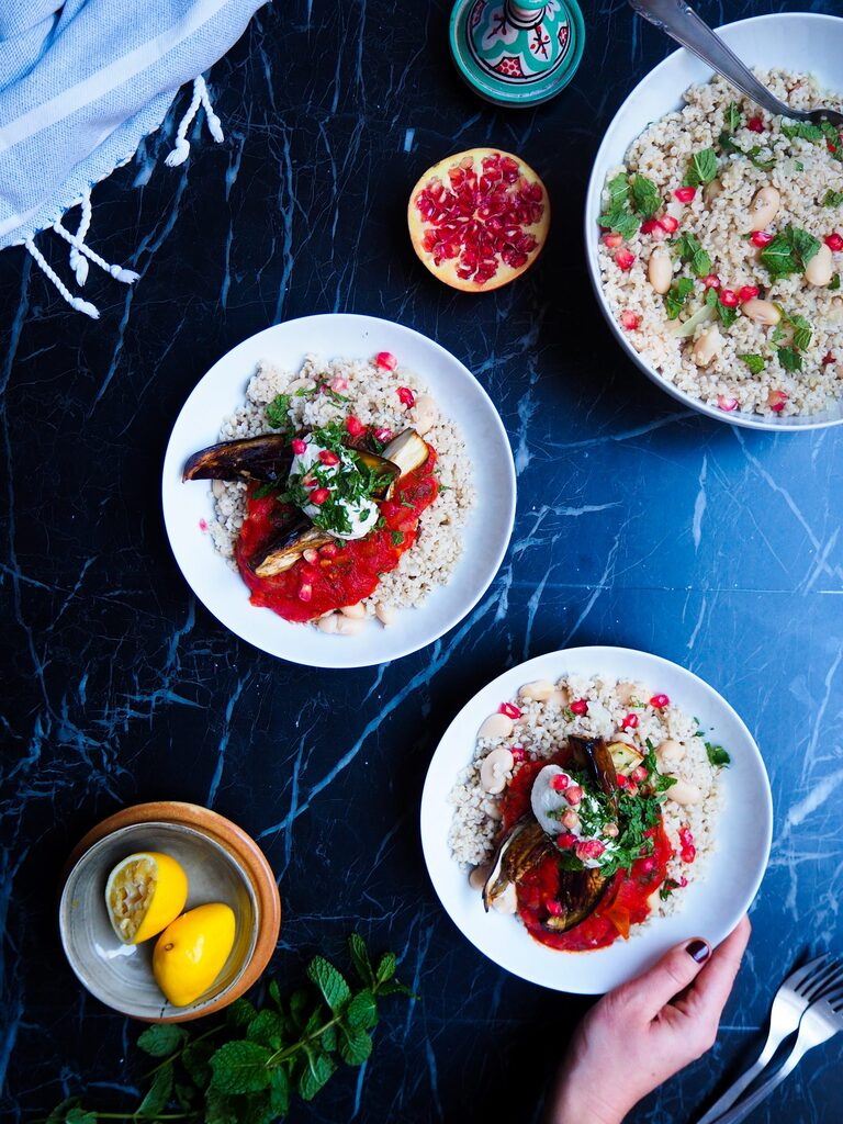 two bowls of vegan borani banjan seen from abotve with a right hand grabbing the bottom bowl, some mint in the left corner, two lemons, a big bowl of semolina in the top corner and half a pomegranate