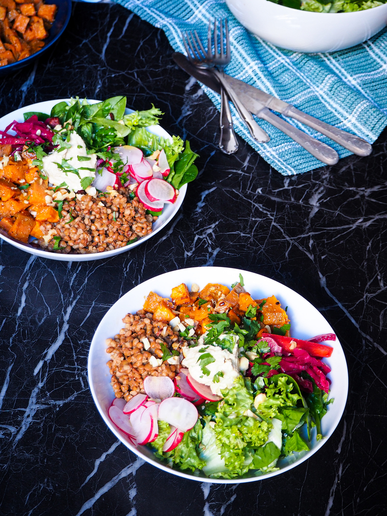 two spiced lentil and sweet potato bowls seen from a front view with some cutlery in the background