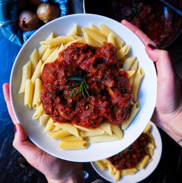 a bowl of penne with mushroom tomato ragú seen up close held up by two hands. in the background is another bowl and a pan with more ragú.