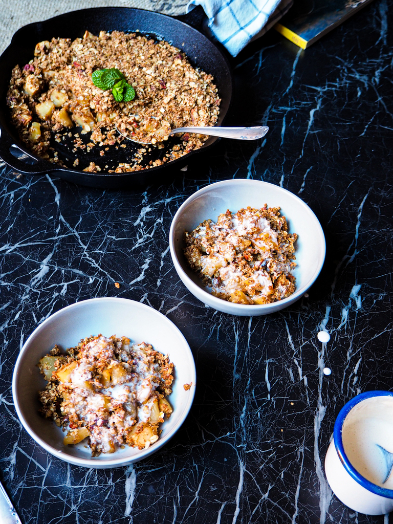 a skillet with vegan apple crumble and two bowls seen from a front view against a dark backdrop