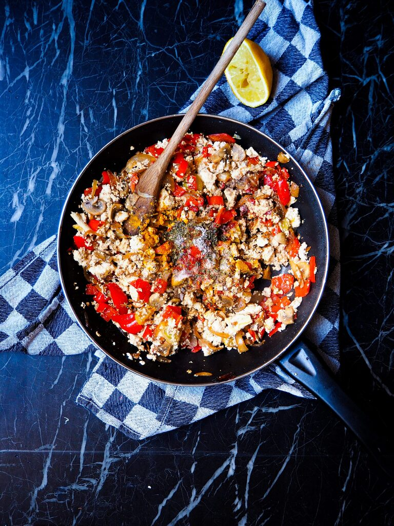 frying pan with tofu scramble seen from above with a wooden spoon and a half a lemon in the top right corner