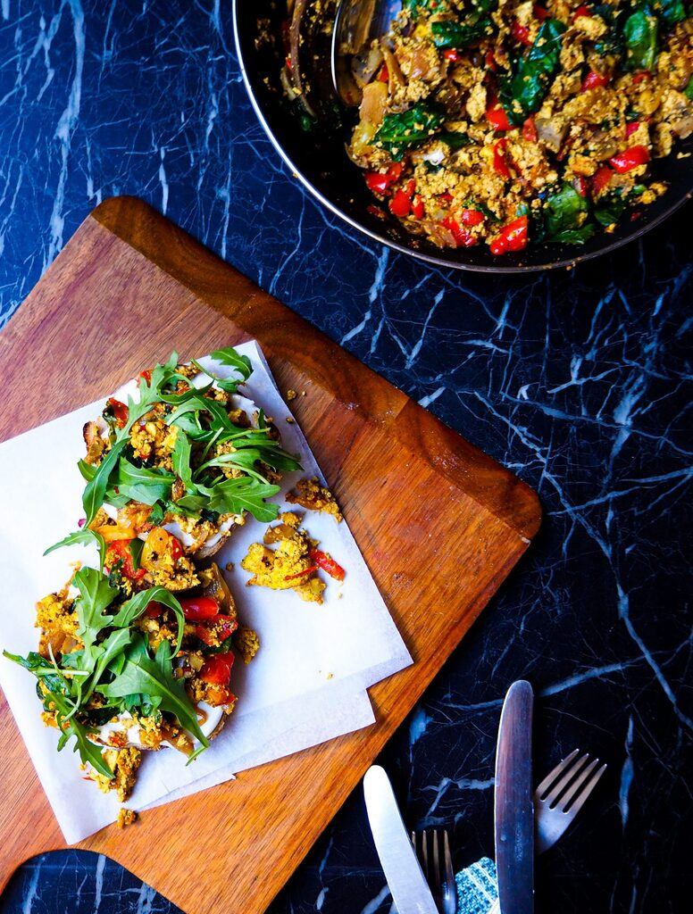 two pieces of toast with loaded tofu scramble on a wooden serving plank with cutlery in the bottom right corner and a frying pan with more of the scramble in the top right corner